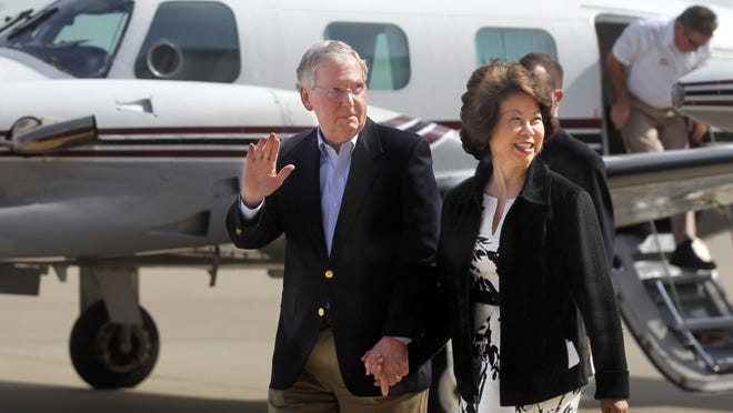 Sen. Mitch McConnell waves to supporters as he arrives with his wife, Elaine Chao, at Cincinnati/Northern Kentucky International Airport for a campaign appearance. Chao is a former U.S. secretary of labor.