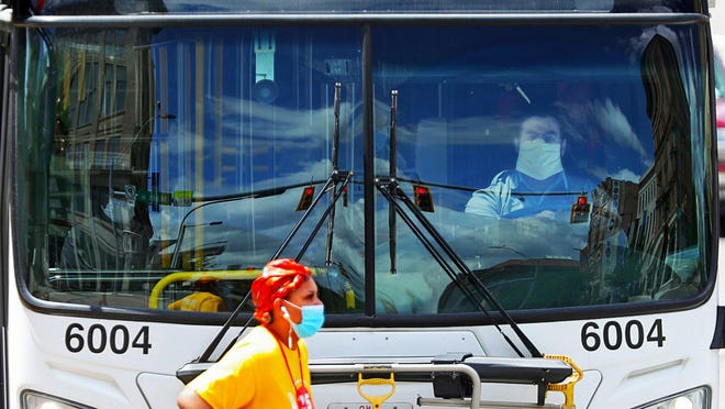A masked pedestrian crosses East Market Street after getting off the bus Saturday in Akron. None of Akron Metro RTA's drivers has tested positive for COVID-19 since instituting mandatory masks in late April when a driver did test positive.