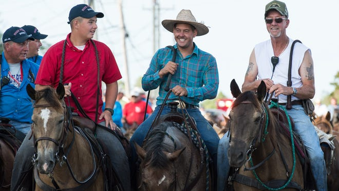 Three Saltwater Cowboys chat during the Chincoteague Pony Parade on Wednesday, July 26, 2017.