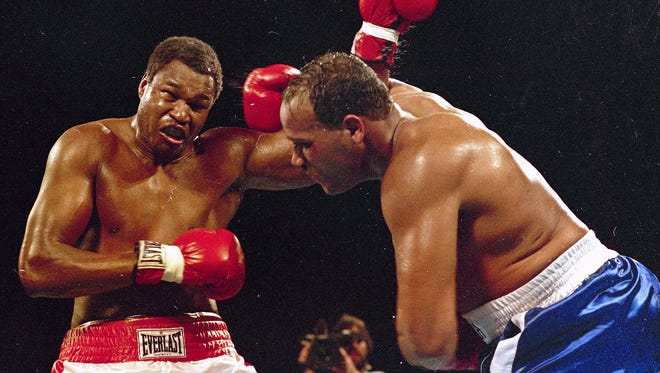this March 15, 1985, file photo, Larry Holmes, left, battles David Bey during a bout in Las Vegas. Bey, a former heavyweight boxing champ from Philadelphia nicknamed 'Hand Grenade,' died Thursday, Sept. 14, 2017, in a construction accident in Camden. Bey was struck by a piece of metal while working on a mixed-use real estate development project, according to the Occupational Safety and Health Administration. He was 60.