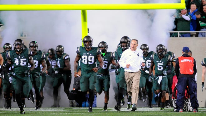 MSU head coach Mark Dantonio leads his team out to take on Oregon at Spartan Stadium in East Lansing Saturday 9/12/2015.