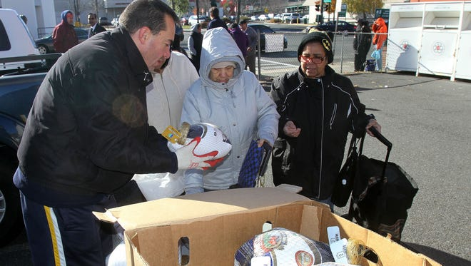 """From left, J.R. Morales hands out turkeys to people during the Food Bank for Westchester's """"Feed a Family"""" project outside of The Salvation Army building in Tarrytown."""