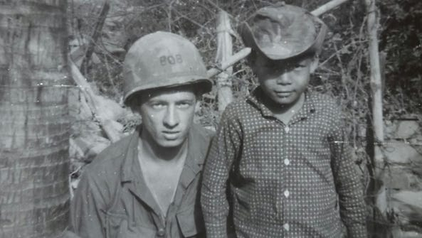 Robert Benson with a Vietnamese child during his time