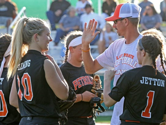 Petrolia freshman Haygen Fleming (10) celebrates with her team and coach Eric Simmons in between innings.