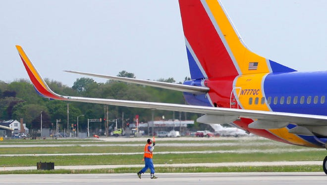 A ground crew member directs a Southwest Airlines flight at Mitchell International Airport in Milwaukee this summer. Passenger traffic was up again in June at Mitchell where Southwest is the market share leader.