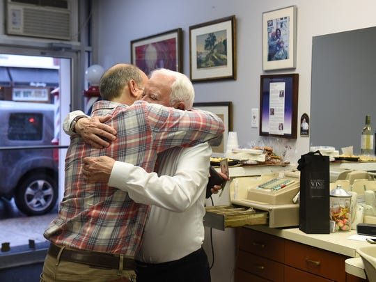 Salvatore Castellano, right, the owner of Sal's Haircutters for Men in Englewood, gives a hug to customer Josh Hyman.