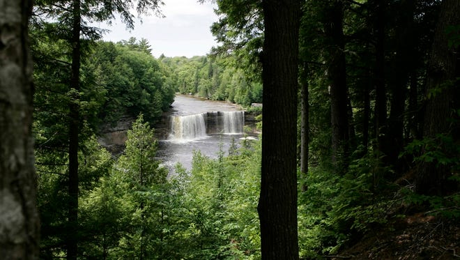"""FILE- In a June 29, 2005 file photo, the Upper Falls at the Tahquamenon Falls near Paradise, Mich., is seen. The state of Michigan wants to help residents and visitors pronounce the names of 2,200 places, people and things in or connected to the Great Lakes state, from Aaliyah (uh-LEE'-uh) to Zilwaukee (zil-WAW'-kee). The Michigan Braille and Talking Book Library recently announced the creation of a guide called """"You Say it How in Michigan?"""" with audio and phonetic pronunciations. The directory was developed for audio book production for the blind and visually impaired, but its writers say the guide can benefit anyone curious about the state of MISH'-uh-gun. (AP Photo/Carlos Osorio, File)"""