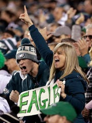 Fans cheer during the first half of the NFL football