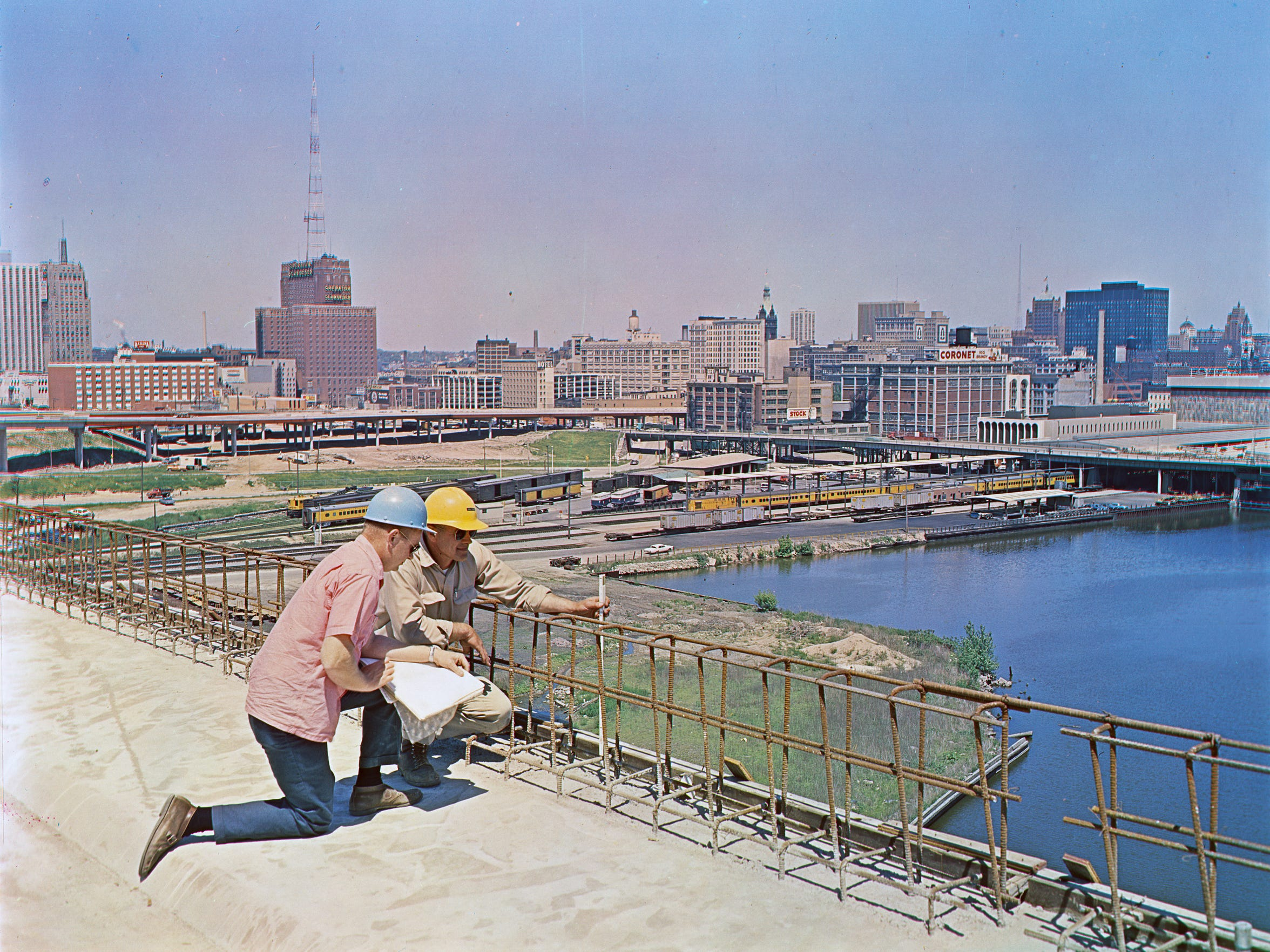 "Construction workers looking over Milwaukee from the north-south freeway that is under construction. This photo was in the June 17, 1968, edition of the Milwaukee Journal with the caption ""Motorists approaching downtown Milwaukee on the North-South freeway later this year will get this view of the skyline as they head north over the Menomonee River valley approaching the central interchange."