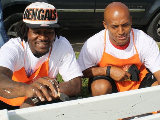 Adam Jones, left, and Leon Hall, seen here volunteering and painting benches at Veterans Park in North College Hill in 2011, will face off Monday night. This is the first game between the friends since Hall left for the Giants this offseason.