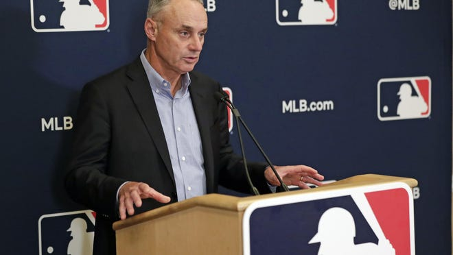 """FILE - In this Feb. 6, 2020, file photo, Baseball Commissioner Rob Manfred answers questions at a press conference during baseball owners meetings in Orlando, Fla. Manfred tells The Associated Press that the commissioner's office, teams and the players' association """"owe it to our fans to be better than we've been the last three months."""""""