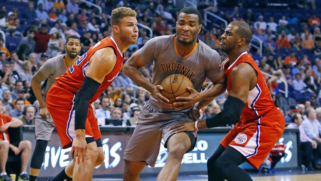 Phoenix Suns forward T.J. Warren (12) drives to the net between Los Angeles Clippers forward Blake Griffin (32) and guard Chris Paul (3) in the first half of  their NBA game Tuesday, April 14, 2015 in Phoenix.