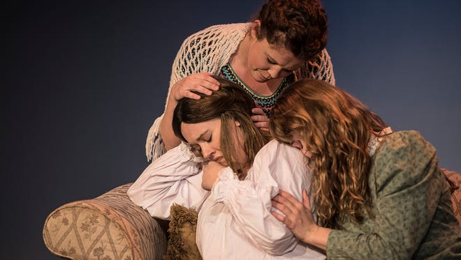 "Joe March, played by Elizabeth Johnson, is comforted by her sisters as she mourns the loss of the long hair she had cut to help raise money for her family in the play ""Little Women."""