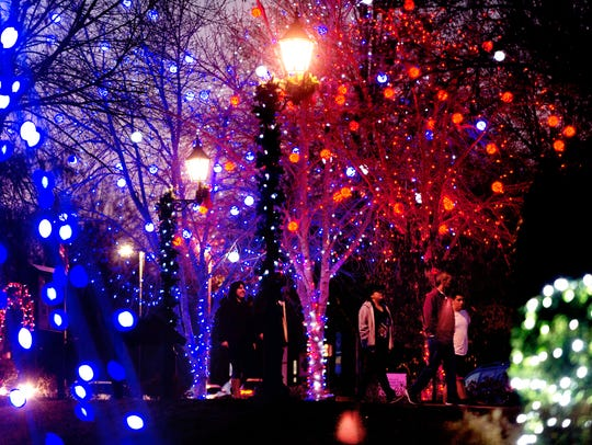 Visitors walk under the lights at the Light the Park