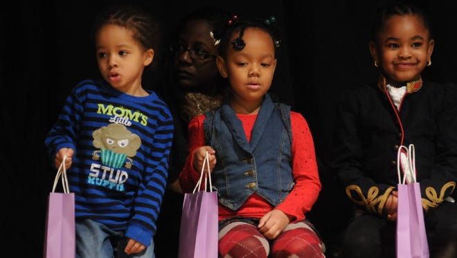 Children from the Catharine Street Community Center sit on stage at the end of the Martin Luther King Jr. breakfast to give out small gifts to the patrons.