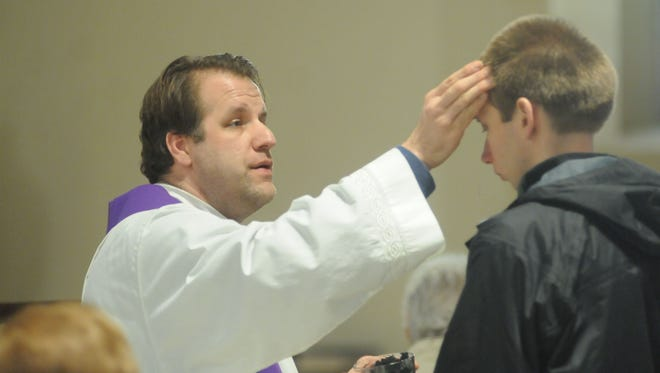 Father Robert Repenning, a pastor at Church of the Holy Trinity in Poughkeepsie, gives ashes to Jacob Morrison of LaGrange at a 12:30 p.m. mass on Ash Wednesday.