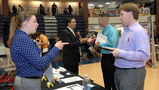 John Niemiec of Howell (right) speaks with Rachel Traub, representing F&W Fitness & Wellness Professional Services at a 2015 job fair at Brookdale Community College in Middletown.