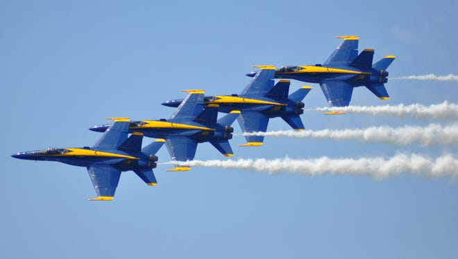 The Blue Angels F/A-18 Hornets fly in a tight diamond formation maintaining 18-inch wing tip to canopy separation.