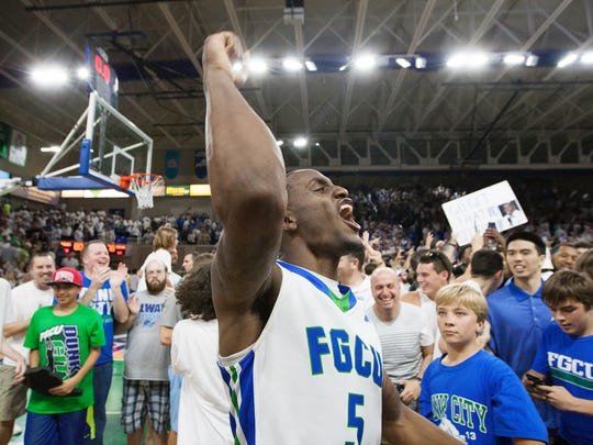 Zach Johnson of the FGCU men's basketball team raise his arm to the fans at Alico Arena in Fort Myers on Sunday after the Eagles defeated Stetson, 80-78, in overtime to advance to the NCAA men's basketball tournament.