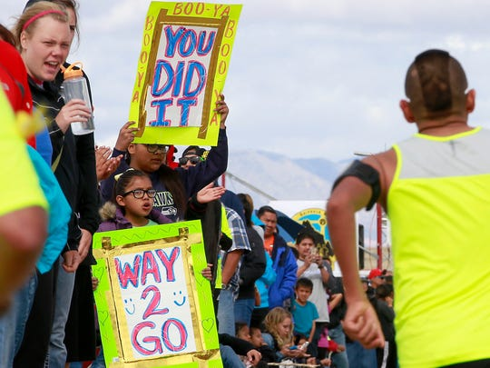 Kira Sam, 7, front, and Bianna Maria, 10, both of Farmington, cheer on the runners during the Shiprock Marathon on May 7, 2016, in Shiprock.