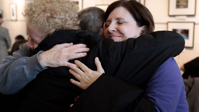 Susan Horowitz, left, and Judy Valenti, right, hug a friend in Ferndale, Mich., on March 21, 2014, after a federal judge strikes down Michigan's ban on gay marriage.
