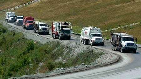 A line of Rumpke trucks work their way up the side of Rumpke landfill in Colerain Township.