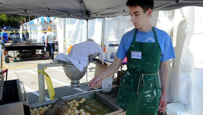 Matthew Panesis cooks loukoumades (Greek honey puffs) at last year's Ventura County Greek Festival at the Camarillo Airport. This year's festival starts Friday night and runs through Sunday.