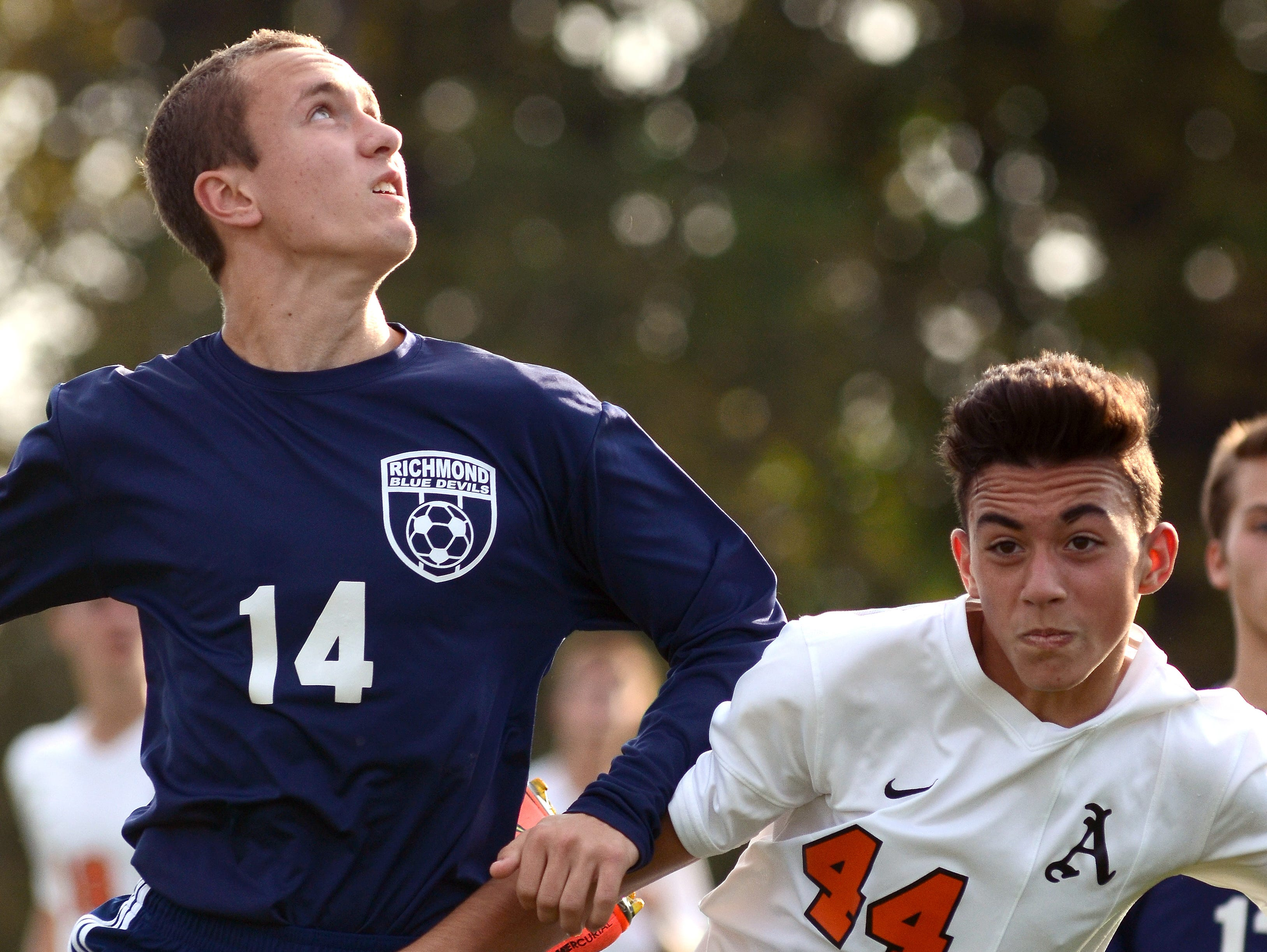 Blue Devils' Evan Quigley and Almonts' Nick Ferrante get tied up as they battle for the ball Monday, Oct. 12 during high school soccer action at Almont.