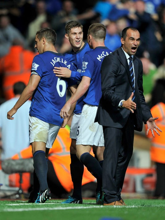 Everton's Phil Jagielka left, celebrates with his manager Roberto Martinez right, after he scored the first goal of the game for his side during their English Premier League soccer match against Liverpool at Anfield in Liverpool, England, Saturday Sept. 27, 2014. (AP Photo/Clint Hughes)