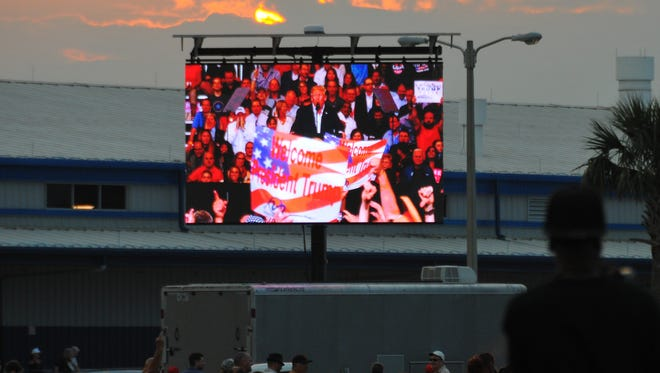 As the sun sets in the west, people outside the hangar watch president Trump on two giant tv screens set up outside. Trump protesters lined up on Apollo Blvd.  in the free speech zone across from the hangar where Trump was appearing to protest against him. The number of protesters reached well over 1000 people with some estimates as high at 1500.