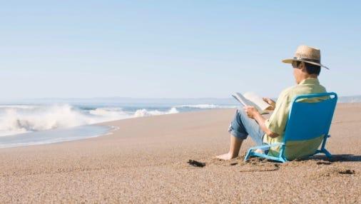 Man reads a book on a beach.
