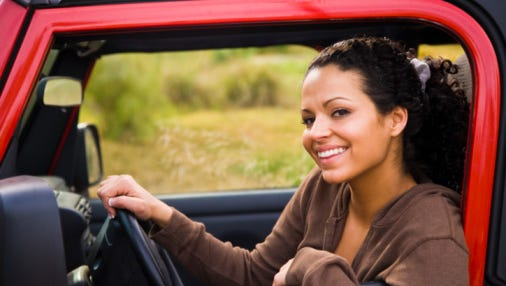 Portrait of a woman sitting in a car and smiling.