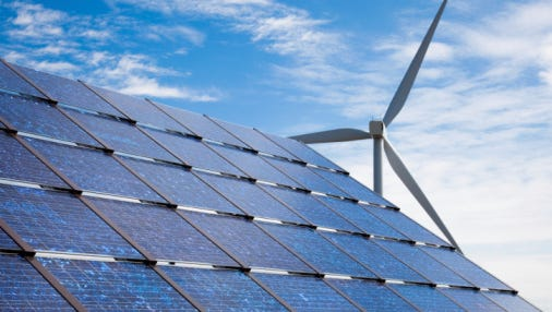 Solar panels with wind turbine in the background