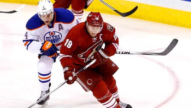 Taylor Hall (4) of the Edmonton Oilers chases down Shane Doan (19) of the Coyotes during the first period of an NHL hockey game Tuesday, December 16, 2014, at Gila River Arena in Glendale, Az.