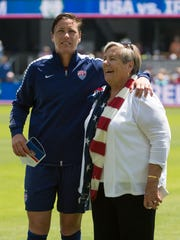 USA forward Abby Wambach (20, left) is escorted onto the field by her mom Judy Wambach (right) before the match against Ireland.