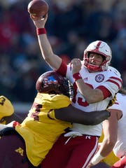 Nebraska quarterback Tanner Lee (13) passes under pressure from Minnesota defensive lineman Merrick Jackson (93) during the second quarter of an NCAA college football game on Saturday, Nov. 11, 2017, in Minneapolis. (AP Photo/Hannah Foslien)