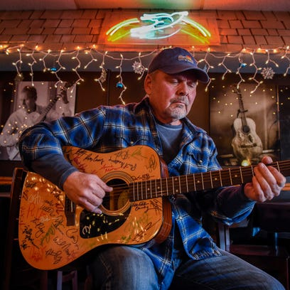Songwriter Kent Blazy plays a guitar that has the signatures