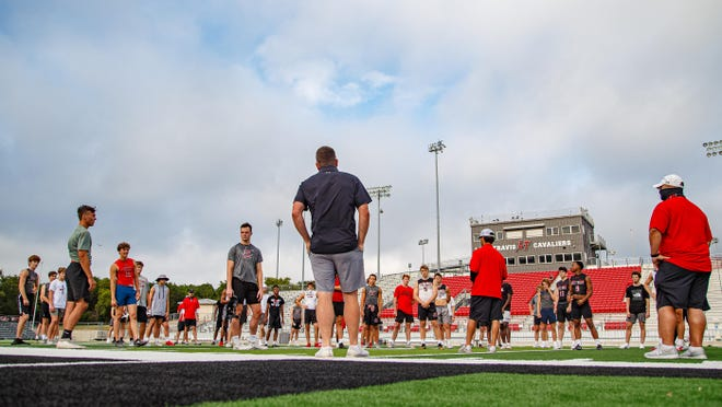 Lake Travis head football coach Hank Carter, center, addresses his offensive team during summer conditioning workouts on June 18 at Lake Travis High School.