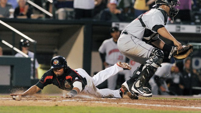 Rochester's Eric Farris, left, touches the plate behind Indianapolis catcher  Omir Santos to score the game-winning run during regular season game played at Frontier Field on July 26, 2014.