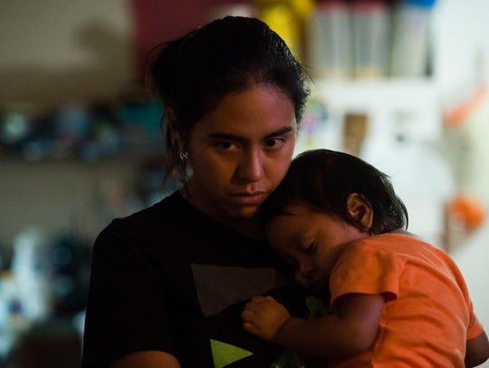 Yahel Salazar holds her son Moises Ramirez in their