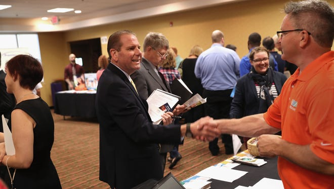 A man speaks with potential employer (right), at a job fair on September 13, 2016 in Hartford, Connecticut.