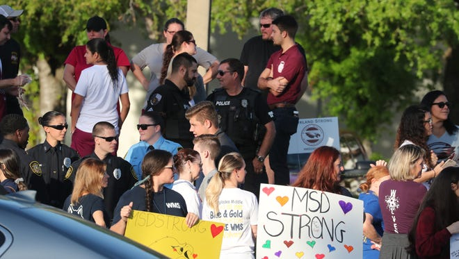 People stand outside the entrance of Marjory Stoneman Douglas High School to greet students as they enter the school grounds on Wednesday, Feb, 28, 2018.