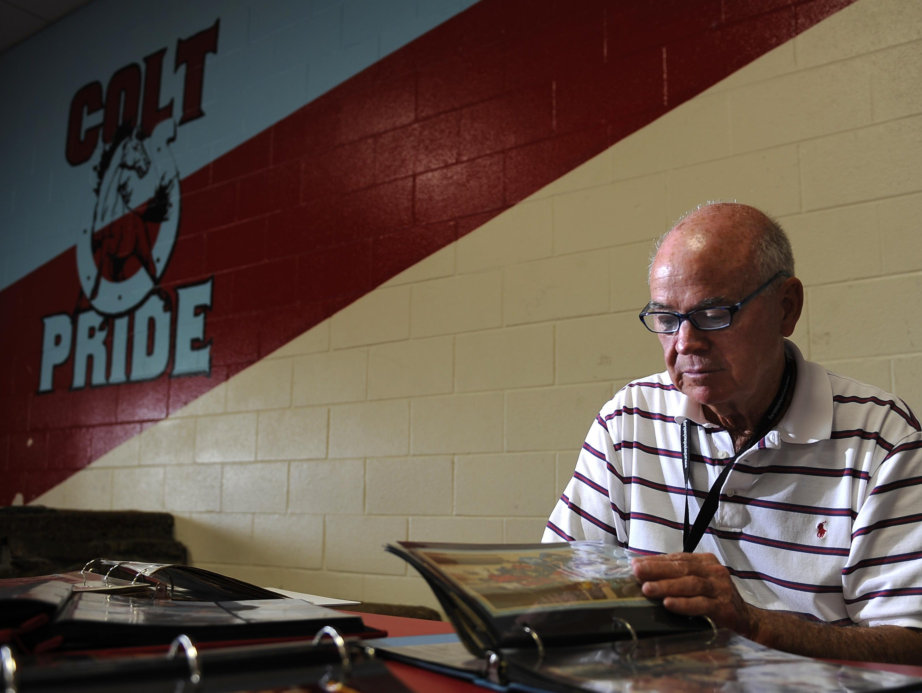 Coach Glenn Falls looks through scrapbooks commemorating his years of coaching in Metro. Falls recently was namedthe girls basketball coach at Martin Luther King. He also coaches volleyball at Glencliff.