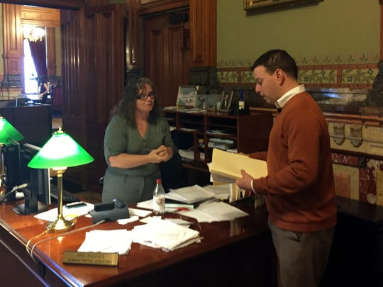 Matt Sinovic, executive director of Progress Iowa, a liberal advocacy group, hands over petitions Thursday with the names of more than 2,500 people to Ann Hughes, an administrative assistant in Gov. Terry Branstad's office. The petitions are opposed to plans to have private organizations take over operations of state mental health institutes in Clarinda and Mount Pleasant.