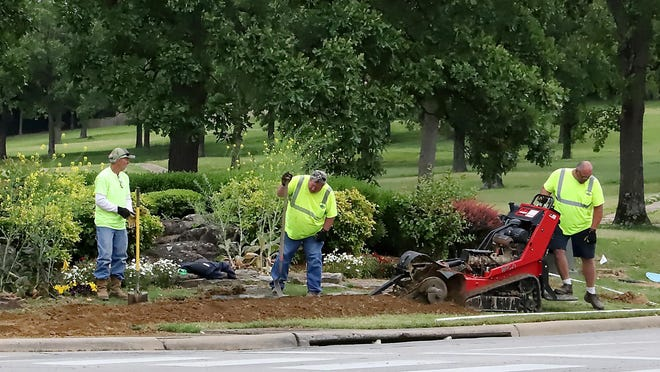 Fort Smith Parks Department workers install a new irrigation system to the Fianna Hills entrance in May 2020.