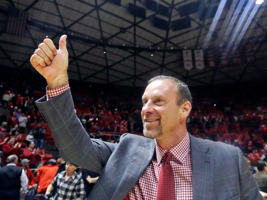 Utah head coach Larry Krystkowiak gives a thumbs-up as he walks off the court after an NCAA college basketball game against Washington State, Sunday. Utah won 88-47.