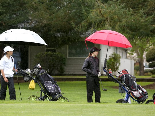 Ashley Zhu, left, a freshman from South Salem, and Jessica Braun, of North Salem, wait under their umbrellas before teeing off Monday at the Greater Valley Conference golf meet at McNary Golf Club in Keizer.