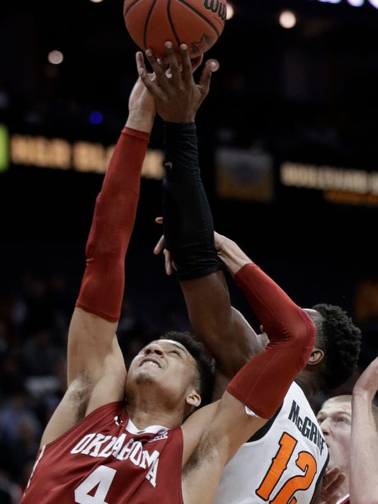 Oklahoma center Jamuni McNeace (4) reaches for a rebound against Oklahoma State forward Cameron McGriff (12) during the first half of an NCAA college basketball game in first round of the Big 12 men's tournament in Kansas City, Mo., Wednesday, March 7, 2018. (AP Photo/Orlin Wagner)
