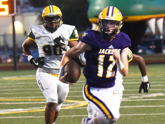 Byrd quarterback Carson Dunn runs away from Captain Shreve defenders during the Yellow Jacket's 34-17 win Thursday at Lee Hedges Stadium.