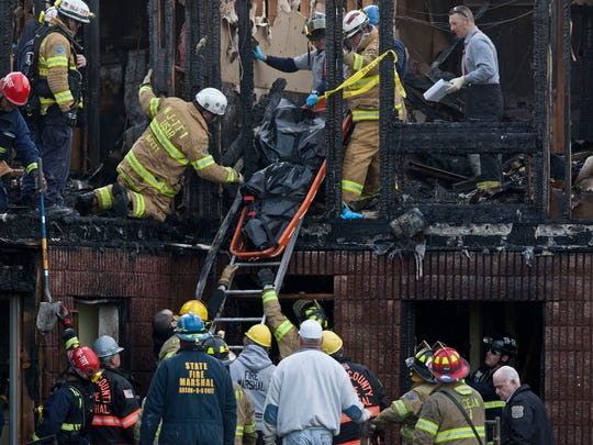 Investigators remove a body from the fatal fire at